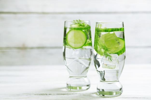 Очки со свежей органической огуречной водой на деревянном столе