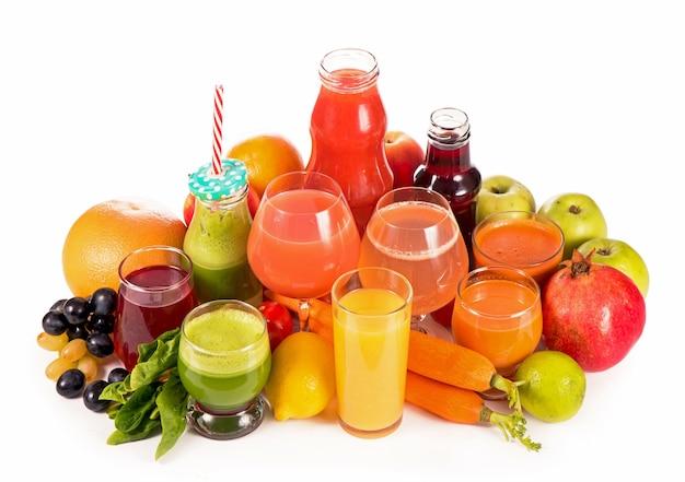 Очки со свежими органическими овощами и фруктовыми соками, изолированные на белом