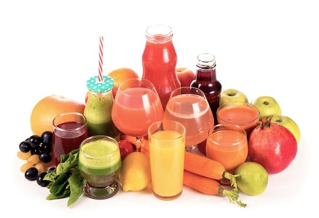 Очки со свежими органическими овощами и фруктовыми соками, изолированные на белом.