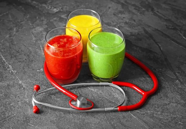 Очки со свежими вкусными коктейлями и стетоскопом на столе. концепция здравоохранения