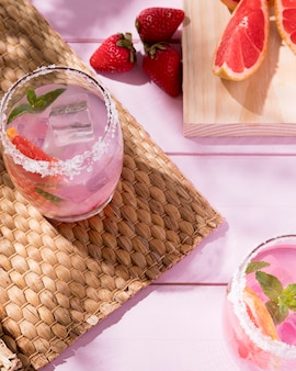 Glasses with grapefruit and strawberry drink on table