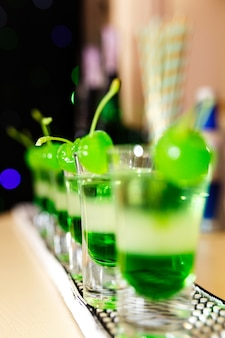 Glasses with green cocktails and green chairs stand on the bar