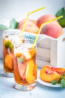 Glasses with homemade ice tea, peach flavored and freshly cut peach slices for arrangement.