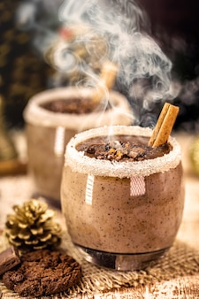 ホットチョコレート、シナモン、砂糖、ミルクが入ったグラス、スチームスモーク、アメリカとヨーロッパの典型的なホットクリスマスドリンク