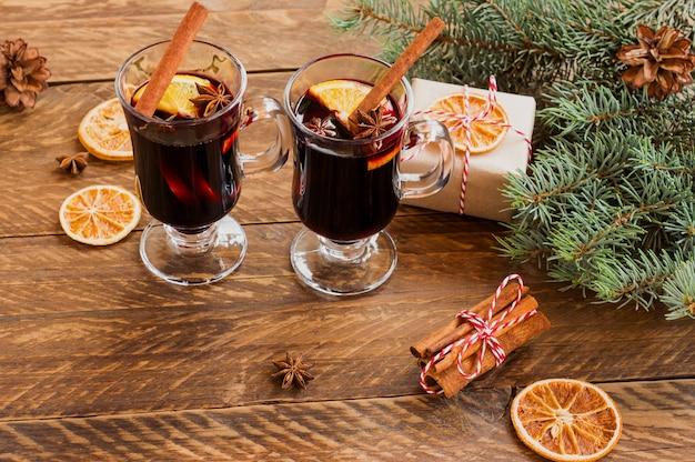 Бокалы с горячим красным глинтвейном на зиму и рождество с долькой апельсина, аниса и палочкой корицы, украшенные еловыми ветками и подарками в упаковке к праздникам. праздничная открытка.
