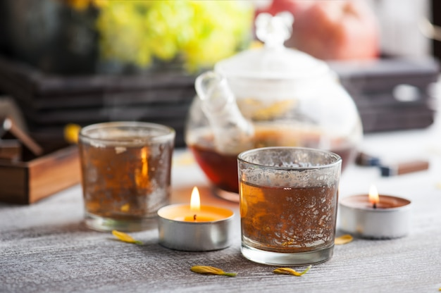 Glasses with lit candles and tea pot
