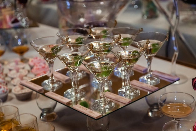 Glasses with martini and green olives stand on mirror tray