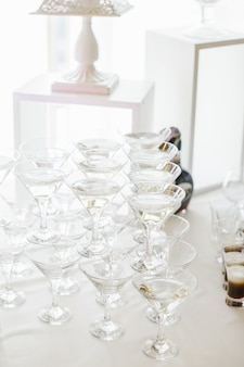 Glasses with martini make a pyramid on white table