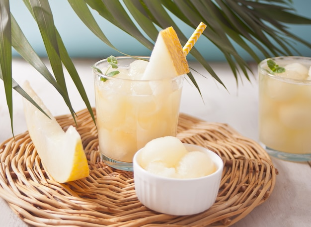Glasses with melon cocktail on a white table with the palm leaf in tropical theme