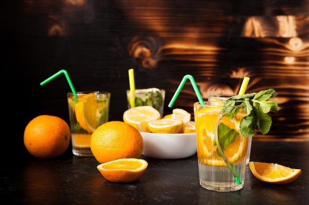어두운 빈티지 나무 배경에 오렌지와 레몬 조각이 들어 있는 천연 물이 든 안경