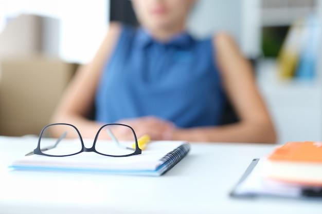 노트북과 문서가 있는 안경은 앉아 있는 실루엣의 배경에 대해 테이블에 놓여 있습니다.