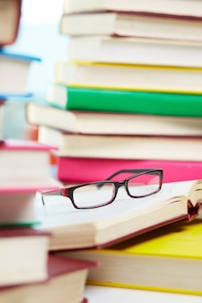 Glasses with a pile of books