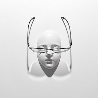 Очки с гипсовой маской для лица с ослабленным зрением, длинные тени на белой стене, копией пространства. вид сверху. оптика моды здорового образа жизни.