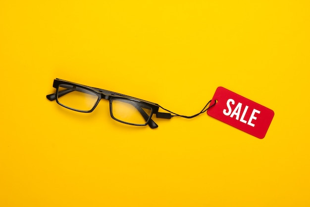 Glasses with red sale tag on yellow.