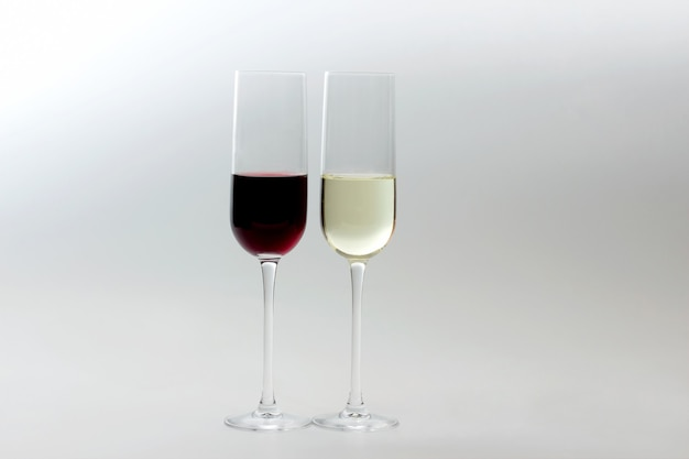 Glasses with red and white wine on light