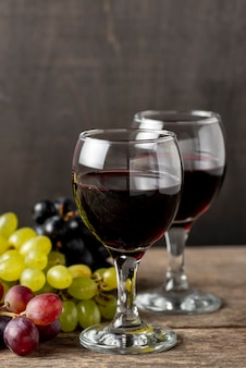 Glasses with red wine beside organic grapes