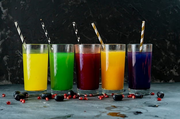 Glasses with red yellow green orange and purple  fresh smoothie on a dark surfaces