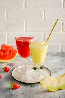 Glasses with red and yellow watermelon juice