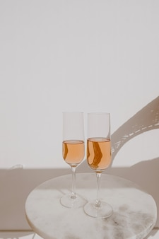 Glasses with rose champagne in sunlight shadows