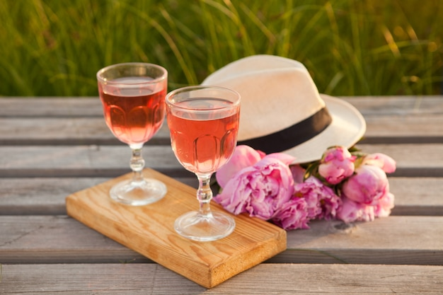 Glasses with rose wine and pink peony bouquet delicious refreshing drink blossoming flower and hat