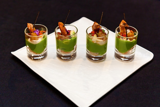 Glasses with seafood and green pasta appetizers banquet platter for events and buffet. catering, shrimp snacks for a banquet.