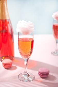 달콤한 솜사탕 핑크 칵테일 및 표면에 병 안경
