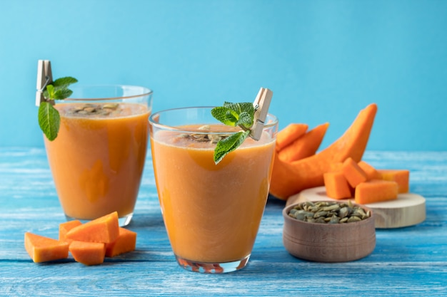 Glasses with tasty pumpkin smoothie on blue wooden table