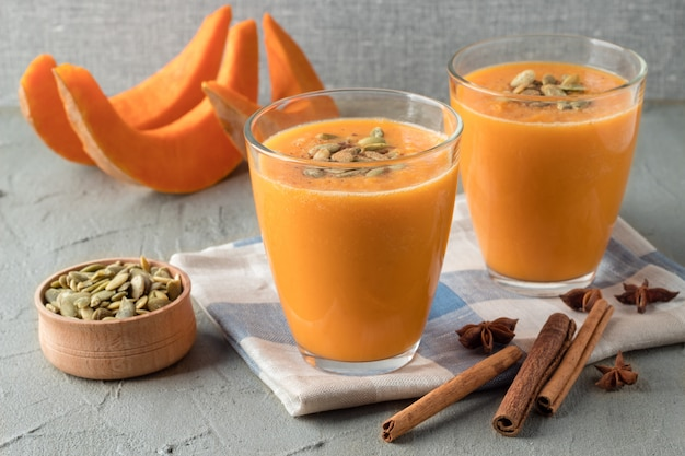 Glasses with tasty pumpkin smoothie on grey table