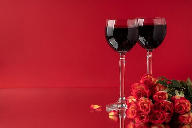 赤い表面においしいワインとバラの花束が入ったグラス、テキスト用のスペース。バレンタイン・デー