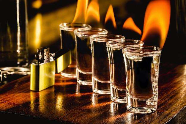 火のテキーラショット、燃えるような飲み物、バーの設定とグラス