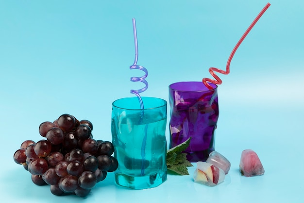 Glasses with water ice cubes and grapes on blue background