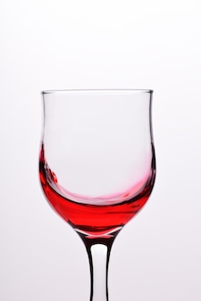 Glasses with waves plash of red wine on a white background