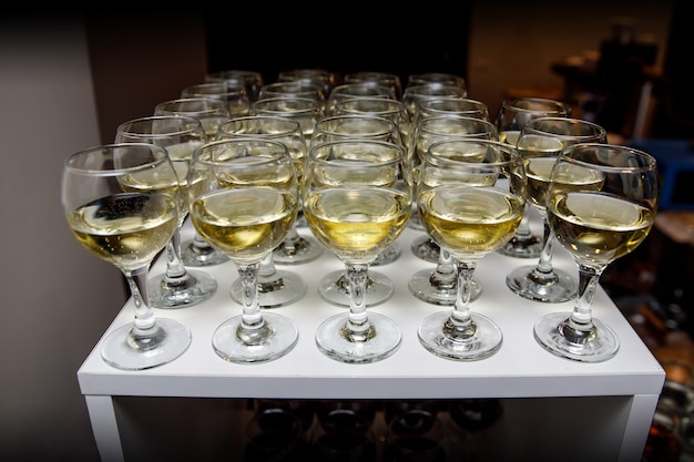 Glasses with white wine on table on event catering