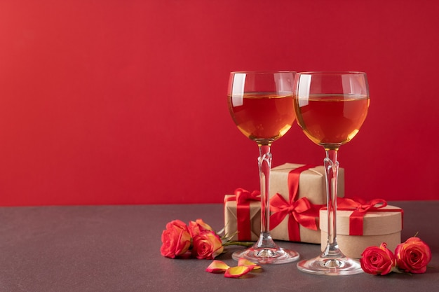 Glasses with wine, gift boxes and roses on table against red background, copy space. valentine's day