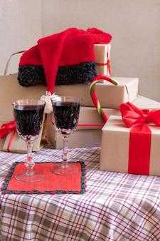Glasses with wine near gifts on the festive table at home