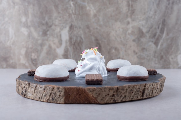 Glazed biscuit and chocolate wafer on board on marble table.