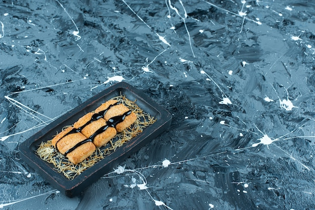大理石の背景に、木の板に艶をかけられたパンくずリスト。