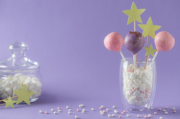 Glazed cake pops in a glass and a jar with marshmallows on a purple wall with sprinkles
