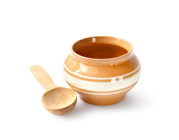 Glazed ceramic pot for cooking with wooden spoon on a white surface