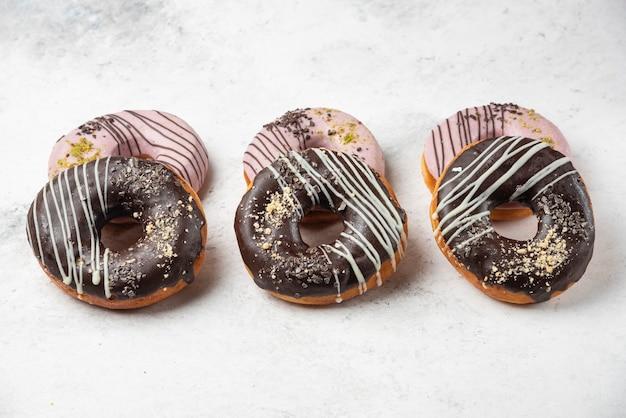 白い表面に艶をかけられたチョコレートとピンクのドーナツ。