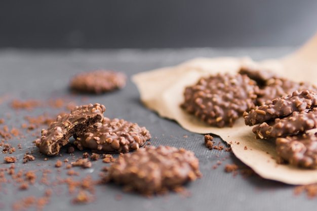 Glazed chocolate cookies with crumbs on craft paper