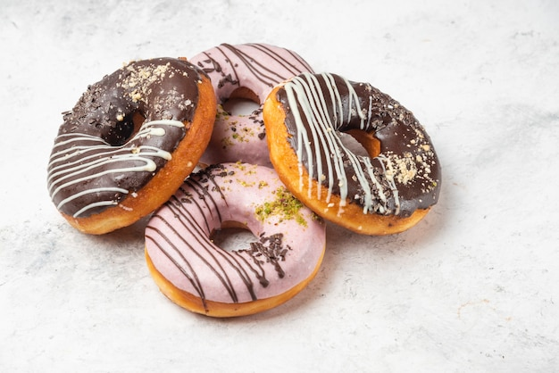 Ciambelle glassate al cioccolato e rosa sulla superficie in marmo.