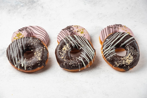 Glazed chocolate and pink donuts on white surface.