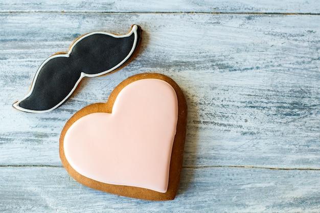 Глазированное печенье в форме сердца. бисквит усов на сером фоне. романтика и изысканность. подарок от настоящего мужчины.