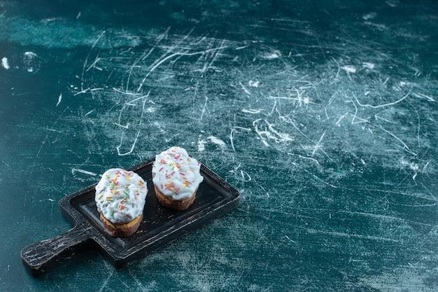 Biscotti glassati su un tagliere, sulla superficie blu