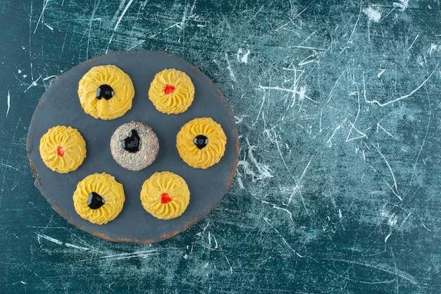 Глазированное печенье на доске, на синем фоне. фото высокого качества