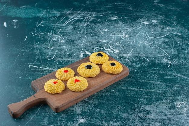 Глазированное печенье на разделочной доске, на синем фоне. фото высокого качества