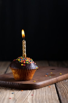 Glazed cupcake with lit candle