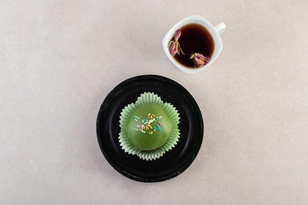 뿌리와 돌 테이블에 차 한잔 유약을 바른 된 컵 케 익.