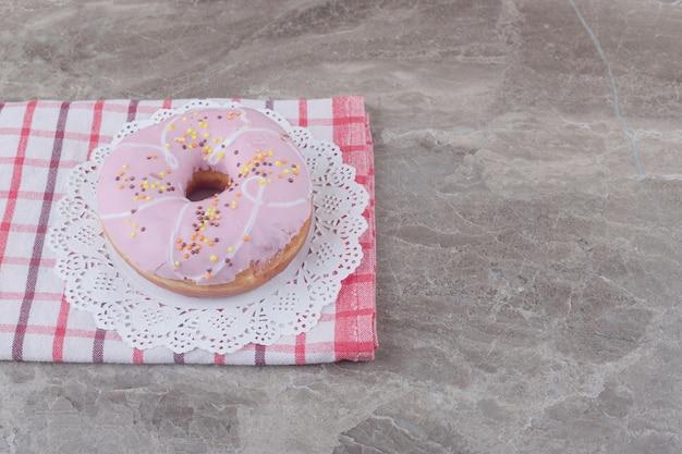 Пончик глазированный на салфетке на полотенце на мраморе